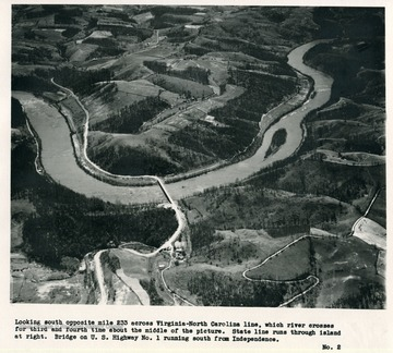 'Looking south opposite mile 233 across Virginia-North Carolina line, which river crosses for third and fourth time about the middle of the picture.  State line runs through island at right.  Bridge on U.S. Highway No. 1 running south from Independence.'