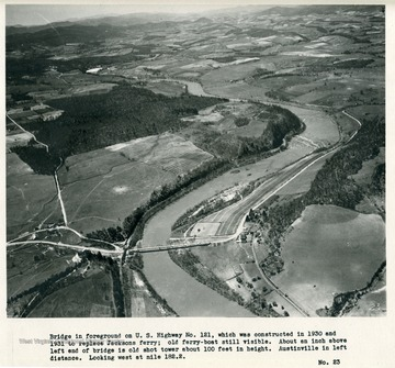'Bridge in foreground on U.S. Highway No. 121, which was constructed in 1930 and 1931 to replace Jacksons ferry; old ferry-boat still visible.  About an inch above left end of bridge is old shot tower about 100 feet in height.  Austinville in left distance.  Looking west at mile 182.2.'