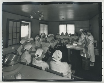 A group of ladies sit in a class, learning how to can food.