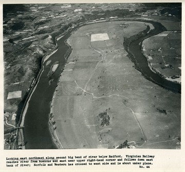 'Looking east northeast along second big bend of river below Radford.  Virginian Railway reaches river from Roanoke and east near upper right-hand corner and follows down east bank of river; Norfolk and Western has crossed to west side and is about under plane.'