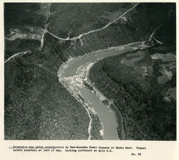 'Diversion dam under construction by New Kanawha Power Company at Hawks Nest.  Tunnel enters mountain at left of dam.  Looking northeast at mile 6.3.'