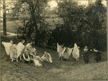 Student performers in togas. One is wearing a horse or donkey head mask.  Taken on school property.