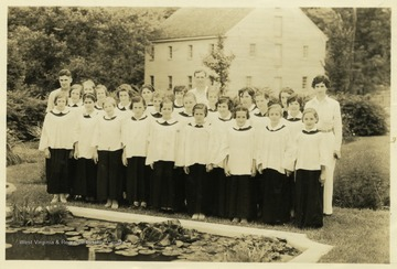 Choir group of girls from 4-H Harrison county camp in front of a pond in a garden.