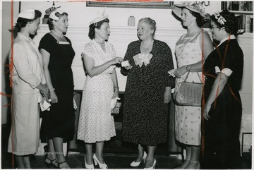 'Pearl Buck, famous Bucks county writer, shown second from right, as she received a membership card in the women's committee of the Delaware Valley Philharmonic Orchestra Association at her home in Dublin.  Mrs. Herbert Alger, chairman of the committee, makes the presentation.  With them (left to right) are Mrs. Donald Seip, Mrs. Oscar Norbeck, and at right, Gloria Gram.'