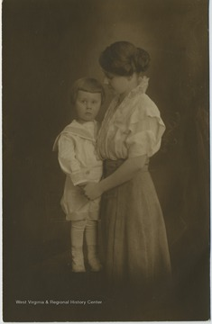 Portrait of a child holding hands with his mother.