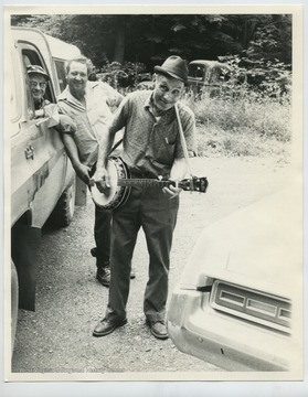 Standing behind Davis is Don Turner; in the truck is Herbert Harper, the mail carrier.  Photo taken in Brushy Run across from Davis' home in Onego.  All three are deceased (2010).