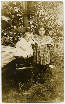A baby seated and a young girl standing.