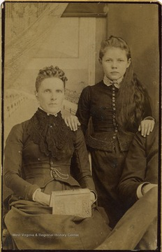 Woman and a girl pose for a formal portrait.