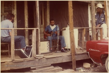 Fred Carper playing the Guitar as Thomas Brown and neighbor listen.
