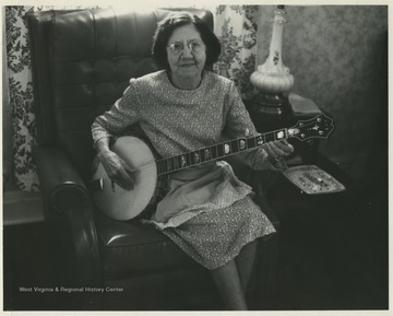 Aunt Jenny Wilson in her living room holding a banjo in her lap.