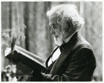 Elderly Pierpont reading a book.