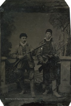 A portrait of two men holding rifles.