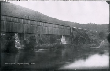 Gen. no. 82, neg. by W, No. 32. Monday 10 A.M. Ford in foreground deep. Dwight and two work men on bridge.