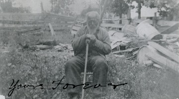 A portrait of a man with a walking stick sitting in a yard. 'From a Helen Ellison photo - copy of an original.'