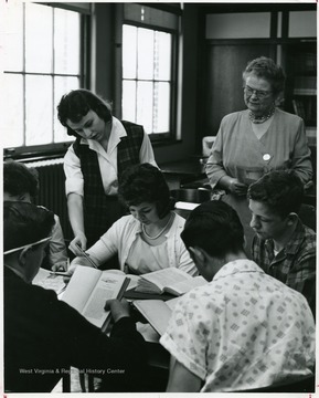 Students grouped around a table with texts in classroom with English teacher,since 1936, Mildred Woofter.