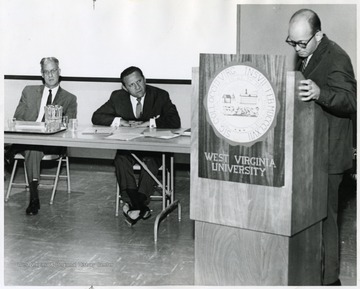 Judge Eddy (seated, first on left) sitting with another man listening to a presentation.