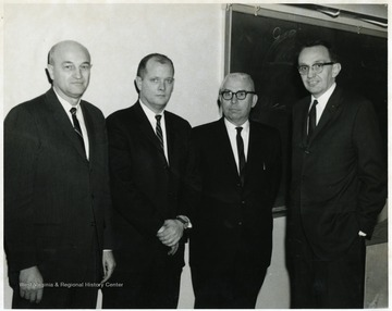 A portrait of Ernest Nesius standing with three other men in a classroom.
