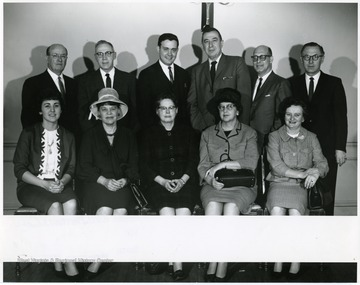 A group portrait of faculty, including Dr. Frasure (standing, far left).