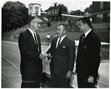 Pete Yost (left), Dean of Physical Education, standing with two other men outside Old Mountaineer Field.