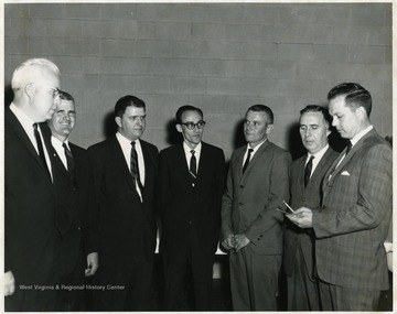 A portrait of Guy Stewart (third from left), Burkey Lilly (far right) and Joe Gluck (second from right) standing with four other men.
