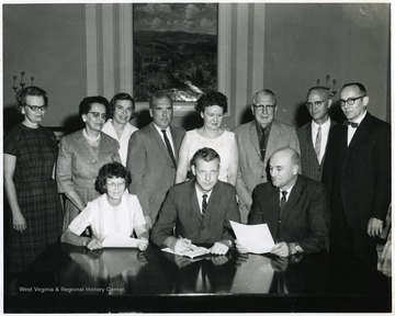 A group photograph inside E. Moore Hall including J.O. Knapp (third from right, back row), Charles Bissett (seated, center) and Mrs. H.D. McGinnis (second from left, standing).