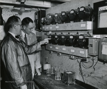 A photograph of Helford Longhouse (left), one time chairman of Agriculture Engineering Department, examining meters with another individual.