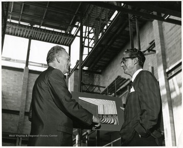 A portrait of Dean Duncan (right), from the Creative Arts Center, examining and discussing a photograph with another man during construction.