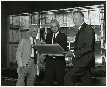A photograph of three men studying information, possibly at the construction site of the Creative Arts Center.
