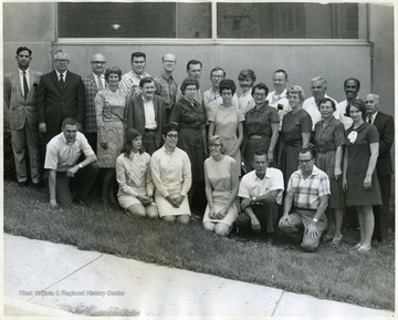 'The ones I know; Back row - Dr. Chak, Dr. I.D. Peters, Dr. Eaves; Second row - Betty Miller, Sam __'  Betty Miller is in the middle row, 6th from the right in the dark colored dress.
