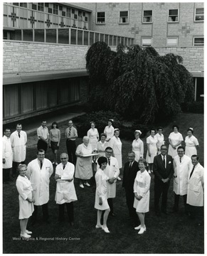 A group portrait of faculty and staff standing outside the WVU Medical Center. Included among the group are Clark Sleeth (front, third from left) and Eugene Stiles (center foreground, dark suit).