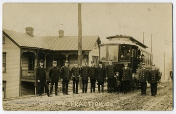 Workers of Grafton Traction company with a car in the background and passengers.