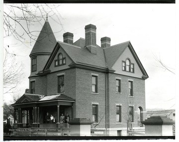 Several unidentified people stand on the front porch of this Queen Anne architectural style house located at 295 Clay Street.