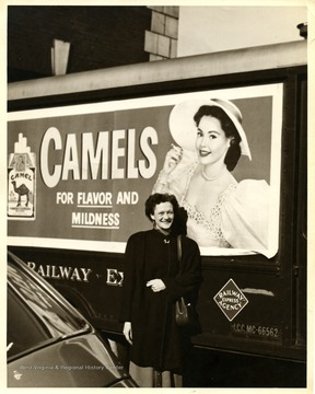 A woman pose in front of a Camel advertisement at B & O Depot.