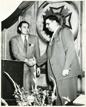 A photograph of Henry Kiser (right) shaking hands with Eugene A. Carter (left).