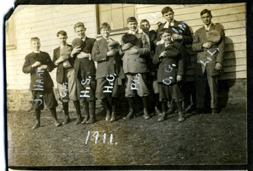 J. Hall is the first boy on the left; every one take its hat and holds it against their chest.