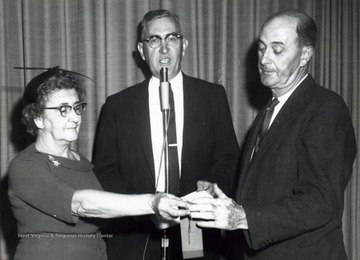 A photograph of Bush Swisher (center) on stage with a man and woman for a presentation.