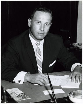 A photograph of Miles Stanley seated at his desk.