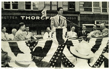 'Philip M. Kaiser, Assistant Secretary of Labor, addresses the 1951 Morgantown Labor Day Celebration.  George A. Crago, third from left, was master of ceremonies for the affair.  Labor and government representatives shown on the speakers stand are, left to right, Richard Kennel, reception committee, commissioner of Labor 1957-.  William Quinn, AFL organizer; Crago, William Radford, AFL labor union; William Hynes, UMW District 4 president, Kaiser, Senator M.M. Neely, State Attorney General William Marland, Eugene A. Carter, state federation of labor AFL president and T. C. Dethloff, AFL organizer.  Senator Harley M. Kilgore was seated directly behind the speaker and is not shown in the picture.
