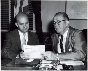A photograph of Senator Hoblitzell (left) and Secretary Benson (right) seated at a desk studying a publication.