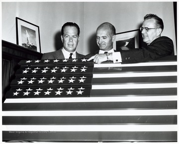 A photograph of Senator John D. Hoblitzell, Jr. (center) and Kaiser Aluminum officials presenting a flag made with aluminum manufactured at Kaiser's Ravenswood, W. Va. plant. At the time of event Senator Hoblitzell lived in Ravenswood.