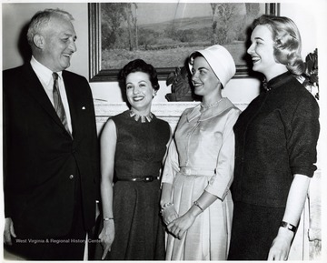 'West Virginia Cherry Blossom Princess - Miss Eleanor Cook of Holden (second from right), West Virginia's princess in the Cherry Blossom Festival, is greeted by Senator Chapman Revercomb (R-WVA) at his Washington office. Miss Cook is flanked by two of her West Virginia attendants, Mrs. Jacquelyne Blake (standing next to the Senator) and Miss Sandra Waggy of Charleston. Both Miss Waggy, who represented West Virginia in the Miss Universe Contest in 1954, and Mrs. Blake are secretaries in Revercomb's office. Miss Cook, daughter of Mrs. Henry H. Cook, Sr., of Holden, is employed as a receptionist for an insurance firm in Washington.; --From Gene Scott'