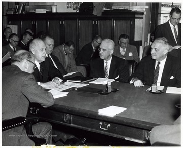 'Interstate Highway Hearings Get Under Way -- Senator Chapman Revercomb (R - WVA), seated extreme right, questions Secretary of Commerce Sinclair Weeks, at head of table, as hearings got under way this week by the Senate Roads Subcommittee on progress of the Interstate Highway System. Department of Commerce officials present for the initial session (seated clockwise) are Louis Rothschild (back to camera), under secretary for transportation; Secretary Weeks; Bradley Nash, deputy under secretary for transportation; and Bertram D. Tallamy, federal highways administrator. Reporters covering the hearing are shown in background.'