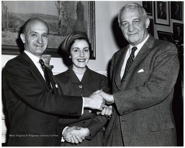 A photograph of Senators Chapman Revercomb and John Hoblitzell, Jr. shaking hands with an unidentified woman.