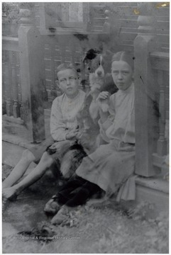 A photograph of a boy and a girl seated on a porch with a dog.