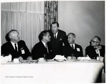 A photograph of Senator Jennings Randolph (standing) behind Harley Staggers (left), Sargent Shriver (second from left), Paul Miller (second from right) and Don Bond (right).