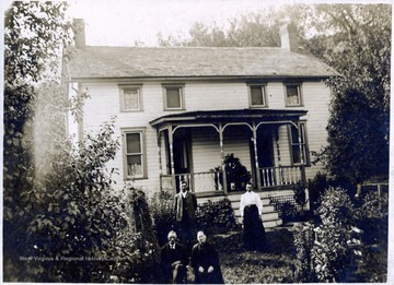A photograph of two men and two women standing in front of a house.