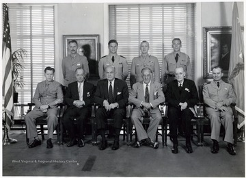 'Sitting, Left to Right: Lt. Colonel A. W. Tyson, USA, Dr. Philip E. Adams, Honorable Louis Johnson, Honorable Stephen Marly, William F. Gibbs, Commander John P. Floyd, USNR; Standing, Left to Right: Lt. Colonel H. L. Conner, USA, Lieutenant (jg) Theodore Hartley, USN, Lt. Colonel Roy L. Kline, USMC, Major Paul Kendall, USAF.'