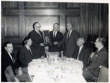 A photograph of Mr. Courtney (third from the left) being presented with a plaque. John Riley is seated on the far left.
