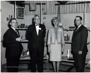 A photograph of Jack Jackson (second from left), Foster G. Mullinax (far right) and two other unidentified individuals in front of an arts and crafts display.