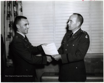 'Col. W. N. Harris, Dir. D/M&TE, presents a letter of Commendation to 2/Lt. David L. Cain, CE Div., for instructor of the month of March 1966.; Publication of this photograph is not authorized unless by a public information office as so noted here - on its use for commercial advertisement must be approved by the Public Information Office of the Chief of Information Department of the Army, The Pentagon Washington 25, D. C. If published please credit as U.S. Army photograph.'